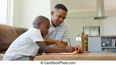 Side view of young black father helping his son with homework in a comfortable home 4k