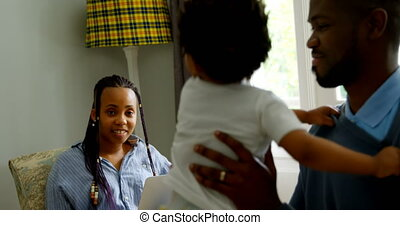 Side view of young black father playing with his son in living of comfortable home 4k