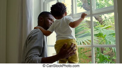 Side view of young black father playing with his son on window sill in a comfortable home 4k