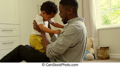 Side view of young black father playing with son on floor in a comfortable home 4k