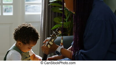 Side view of young black mother and little son playing guitar in living room of comfortable home 4k