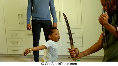 Side view of young black mother and son playing with toy sword in a comfortable home 4k