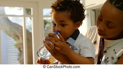Side view of young black mother feeding water to her son in kitchen of comfortable home 4k