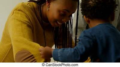 Side view of young black mother playing with her son in a comfortable home 4k