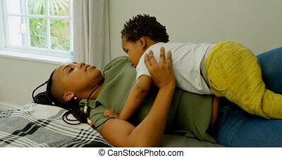Side view of young black mother playing with her son on bed in a comfortable home 4k