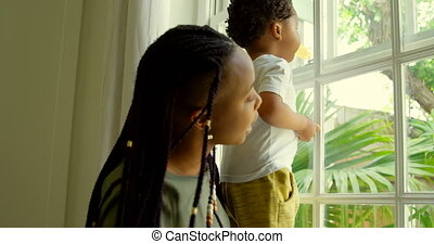 Side view of young black mother playing with his son on ...