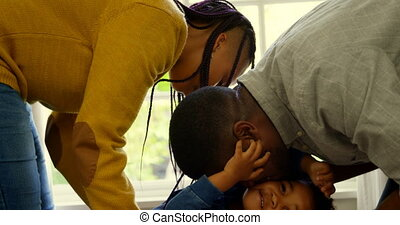 Side view of young black parents playing with their son in a comfortable home 4k