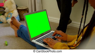 Side view of young black woman using laptop and sitting on floor of comfortable home 4k