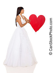 young bride holding big red heart shape