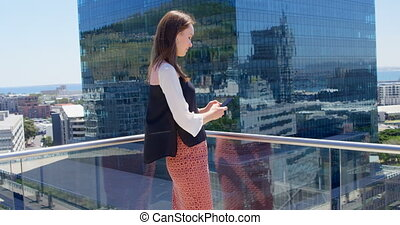 Side view of young caucasian businesswoman texting on mobile...