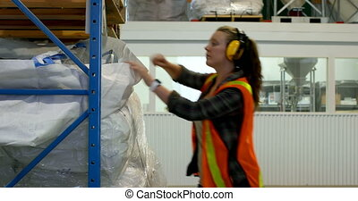 Side view of young caucasian female worker checking stock in...