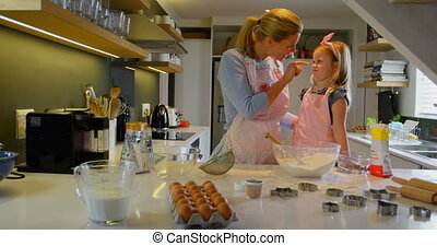 Side view of young Caucasian mother and daughter baking cookies in kitchen of comfortable home 4k