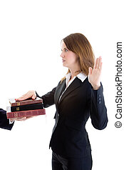 Side view of young Caucasian woman in a suit swearing on a stack of bibles with arm raised.  Isolated on white background.