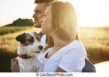 Side view of young couple and dog enjoying the view