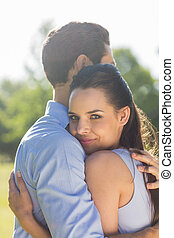 Side view of young couple embracing at park