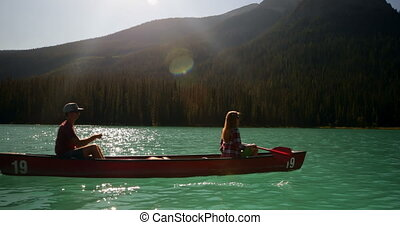 Side view of young couple rowing boat on a turquoise river 4k