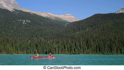 Side view of young couple rowing boat on a turquoise river in the sunshine 4k