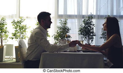 Side view of young couple sitting together at table in...