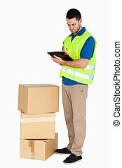 Side view of young delivery man filling in delivery note