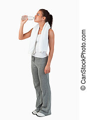 Side view of young female taking a sip of water after training