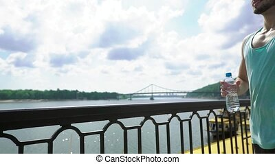 Side view of young handsome runner wearing blue sportswear with water bottle standing on a bridge and enjoying river landscape