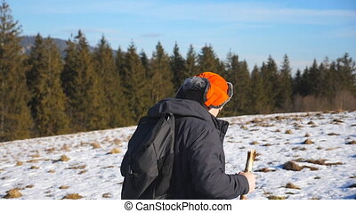Side view of young hiker with backpack and stick in hand climbing on snowy hill in field. Sporty guy hiking on snow meadow at sunny day. Healthy active lifestyle. Winter forest at background