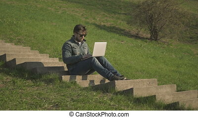 Side View of Young Hipster Man In Sunglasses Sitting On The Stairs Using Laptop