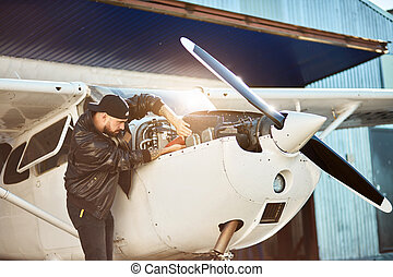 side view of young male engineer inspecting small propeller airplane