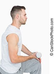 Side view of young man exercising with dumbbell