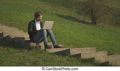 Side View of Young Man Sitting On The Stairs In Park Using Laptop