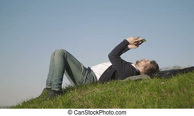 Side View of Young Man Using Tablet PC While Lying On Grass Against Clear Sky