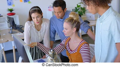 Side view of young mixed-race business people working on desktop pc at desk in modern office 4k