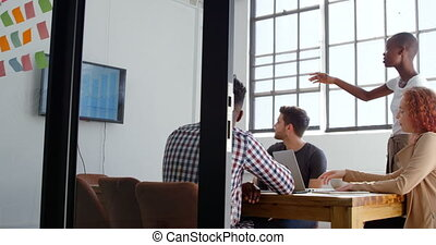 Side view of young mixed-race business team planning and...