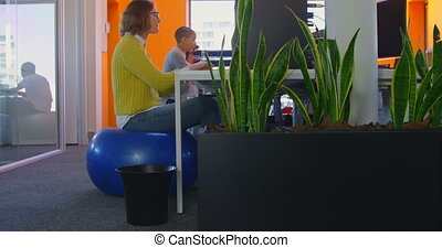 Side view of Young mixed race business team working together at desk in modern office 4k