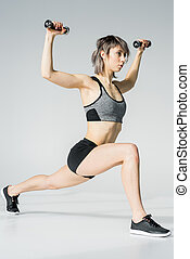 Side view of young sportswoman exercising with dumbbells