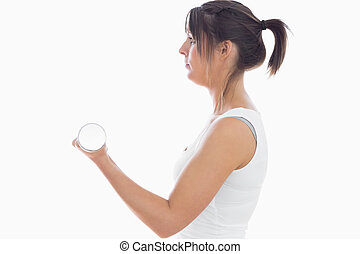 Side view of young woman exercising with dumbbell