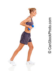 side view of young woman exercising with dumbbells