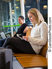 Side View Of Young Woman Reading Book At Airport