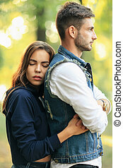 Side view of young woman with closed eyes hugging boyfriend