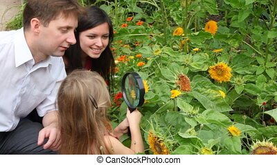 girl and her parents discovering flower with magnifying glass