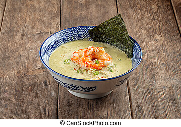 Side view on matcha ramen soup with langoustines