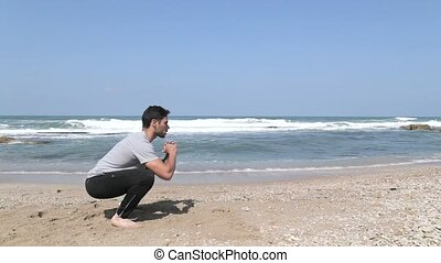 side view on squat exercise on the beach - Man doing squat...