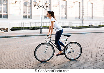 Side view portrait of a beautiful woman riding on bicycle