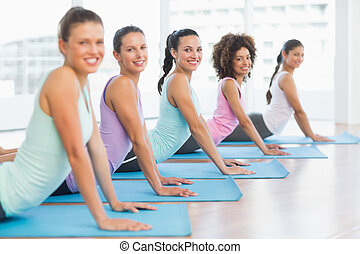 Side view portrait of a fit class doing the cobra pose in a...