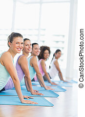 Side view portrait of a fit class doing the cobra pose