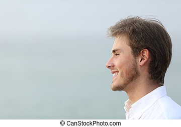 Side view portrait of a happy man on the beach