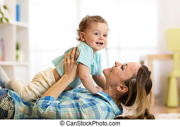 Side view portrait of a happy mother lying on the floor with her baby son