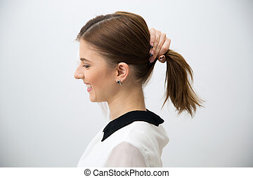 Side view portrait of a happy woman holding her hair