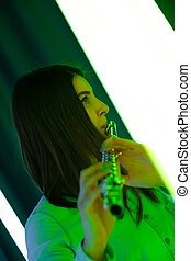 Side view portrait of a pretty young woman musician playing the flute. Female flutist plays wind instrument in a dark studio against the backdrop of bright neon lights. Close up.