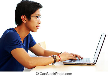 Side view portrait of a young asian man using laptop